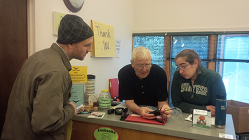 Robert Benton (center), of TASIS Group, shows Simon Solomon and Sarah Freedman how to properly use the commercial UHF radio system he recently donated to Friends for Rogers. Photo courtesy Friends of Rogers