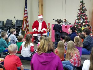 Santa Claus is shown on stage with some of the children in attendance.