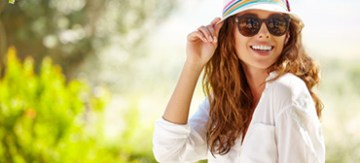 Stylish woman in sunglasses tipping hat brim and smiling