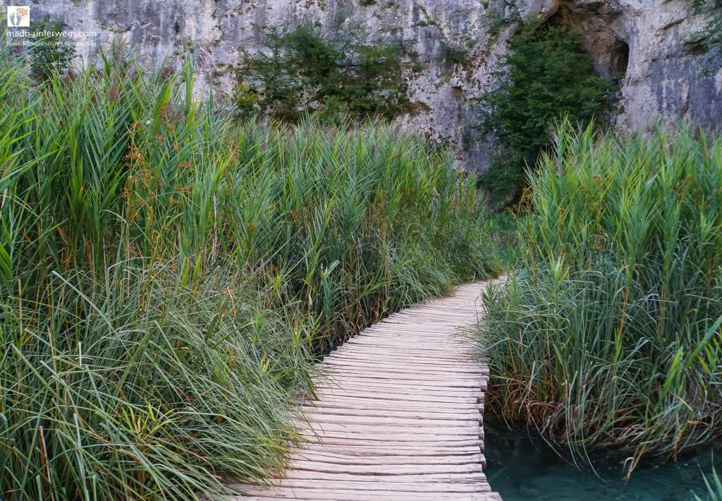 """Holzsteg, der vom Bildvordergrund nach rechts hinten verläuft; links und rechts vom Steg Seegräser; im Hintergrund helles Gestein; links oben Text """"mado-unterwegs.com"""""""