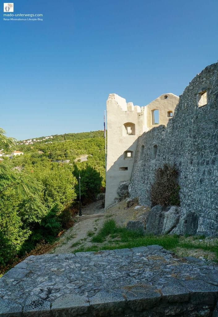 """rechts Blick auf die Außenfront mit verfallen Turm des Fort Trsat, rechts bewaldete Hügel - Rijeka - Kroatien / links oben der Text """"mado-unterwegs.com"""""""