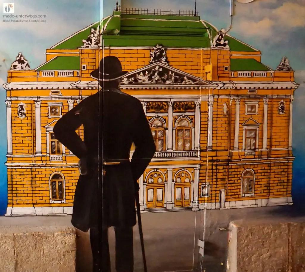 """Street-Art: Abbildung eines Gebäudes, davor steht ein Mann mit Melone und Gehstock – in Rijeka – Kroatien / links oben der Text """"mado-unterwegs.com"""""""