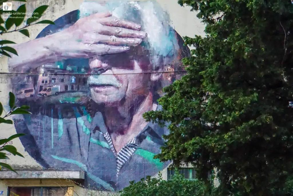 """Street-Art-Mural von Sebas Velasco: Mann mit weißen Haaren hält sich die rechte Hand vor die Augen – in Rijeka - Kroatien / links oben der Text """"mado-unterwegs.com"""""""