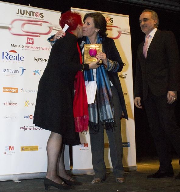 Helena Herrero recogiendo el galardón 'Mujer Directiva 2015' en la Semana Internacional de la Mujer de manos de la periodista Rosa Mª Calaf y de Salvador Molina, vicepresidente de FWW.