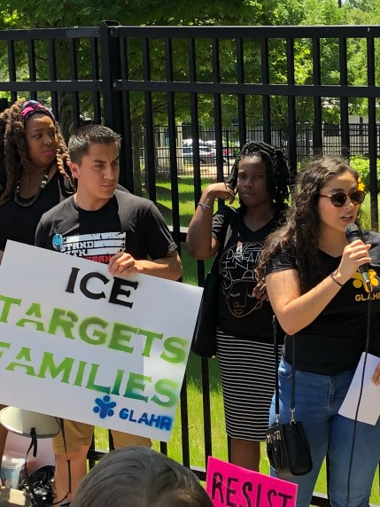 Woman in black shirt and sunglasses speaks into microphone next to man holding ICE targets families sign in front of ICE fence