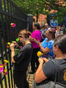 several people along with one woman in black shirt affixing a flower to a black fence