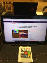 Laptop in Microsoft Store displaying change.org petition, with flyer on keyboard
