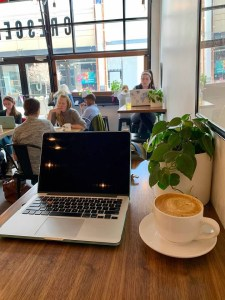 Laptop open at Crescendo coffee shop.