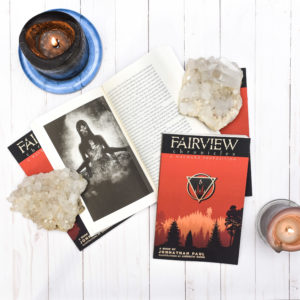 The Fairview Chronicles Vol. 1 arranged on a white washed wood paneling background. Two closed copies prop up a copy which is opened to an image of a woman being disemboweled. Another closed copy and two chunks of quartz hold the book open. Two candles fill negative space on either side of the image.