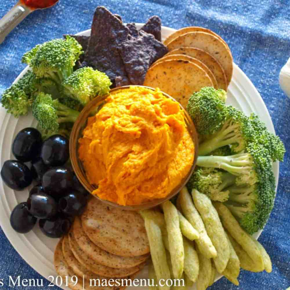 Sweet Potato Hummus with Harissa, veggies, and crackers on a white plate. Garlic clove, tooth picks, harissa, and lemons surround plate and sit on a blue dish towel.