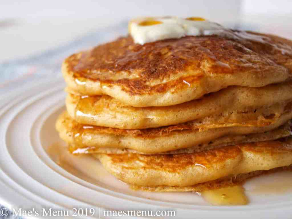 Stack of best whole wheat pancakes with maple syrup and butter.