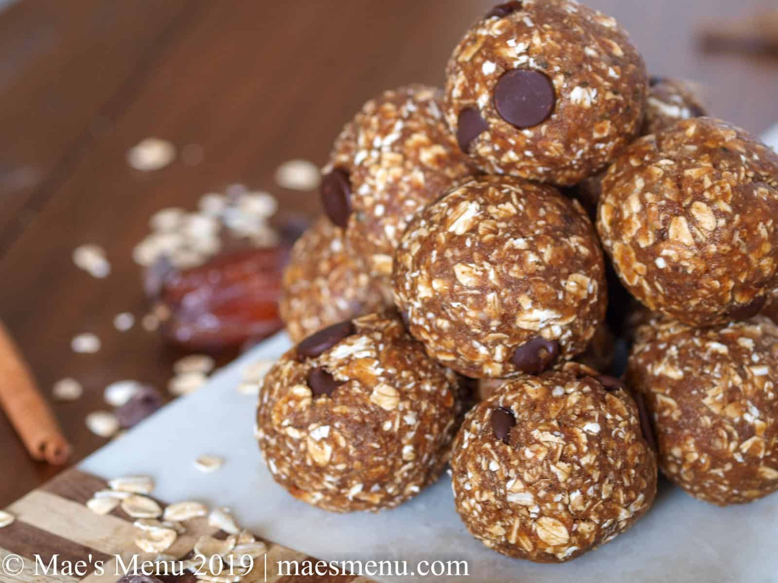 A pyramid of date energy balls on a small serving board.