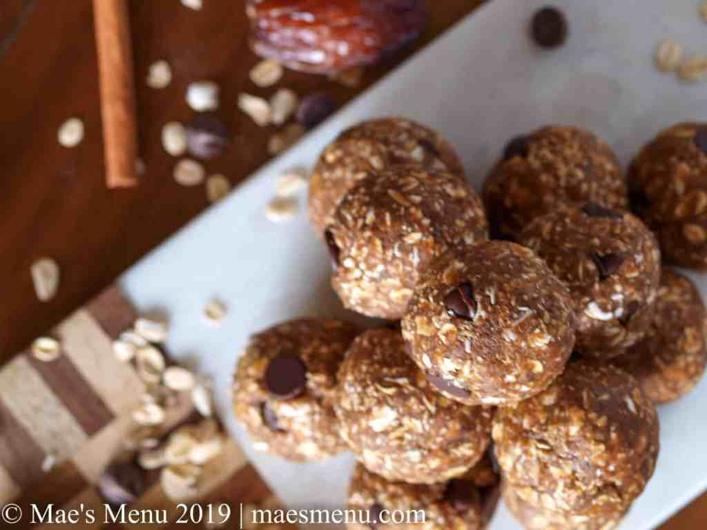 A pyramid of date energy balls on a marble and wood cutting board.