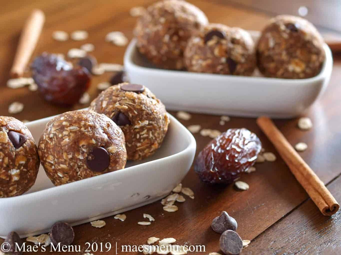 Two small dishes of date energy balls next to dates, oats, cinnamon sticks, and chococlate chips.