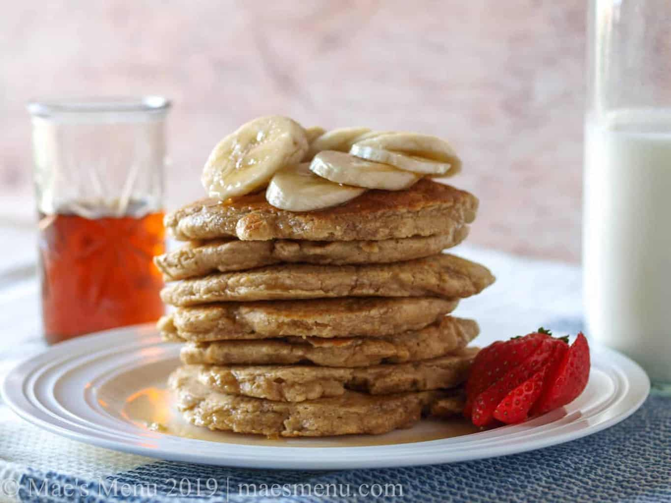 A stack of gluten-free pancakes next to syrup and milk.