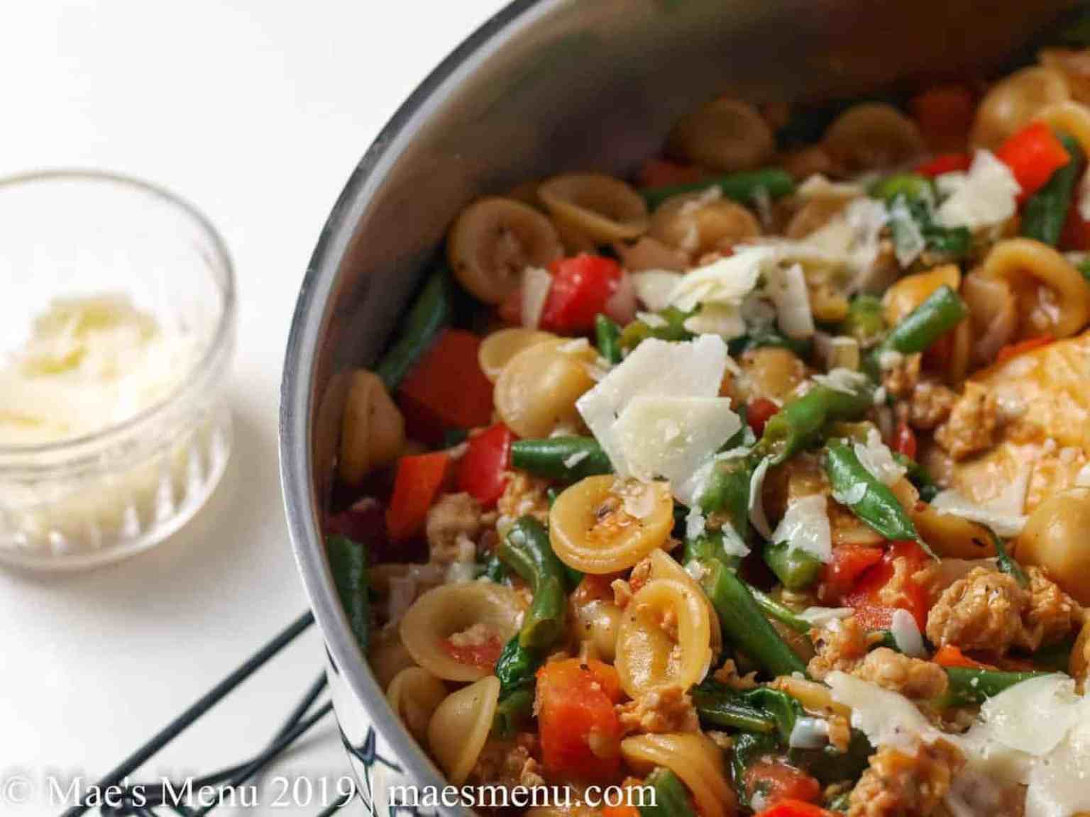 Large saute pan of one pot orecchiette with sausage and a glass ramekin of hard cheese.