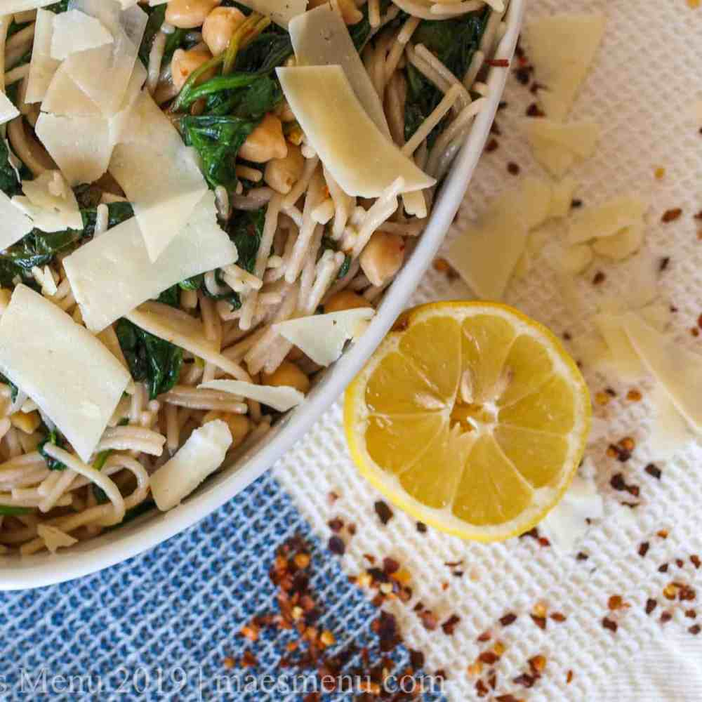 A white serving bowl of Spaghetti with Beans & Garlicky Greens next to a lemon, red pepper, and cheese.