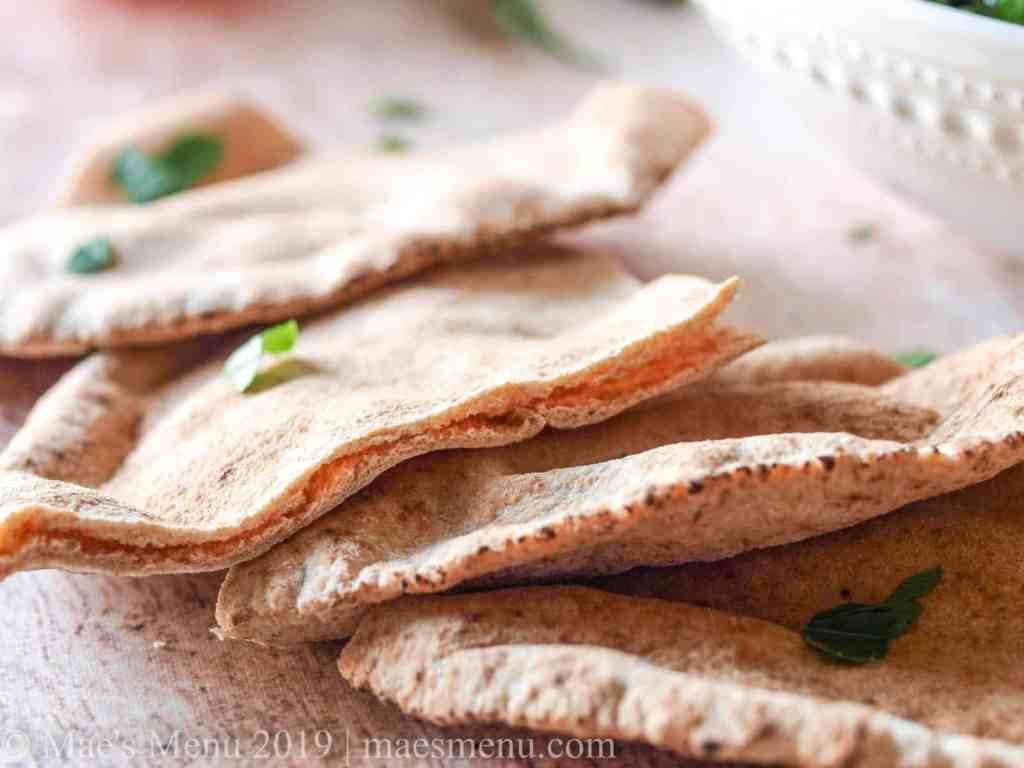 An up-close picture of some slices of pita on a wooden table.
