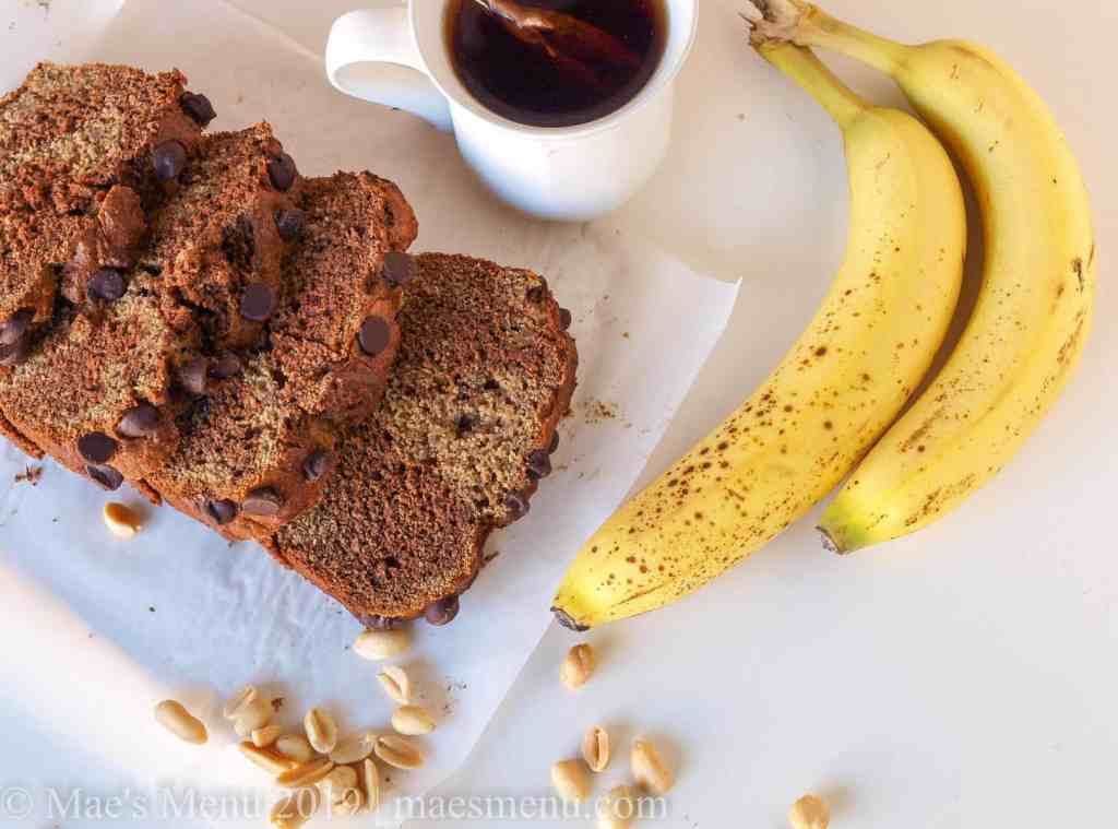 Slices of peanut butter chocolate banana bread next to a cup of tea and bananas.