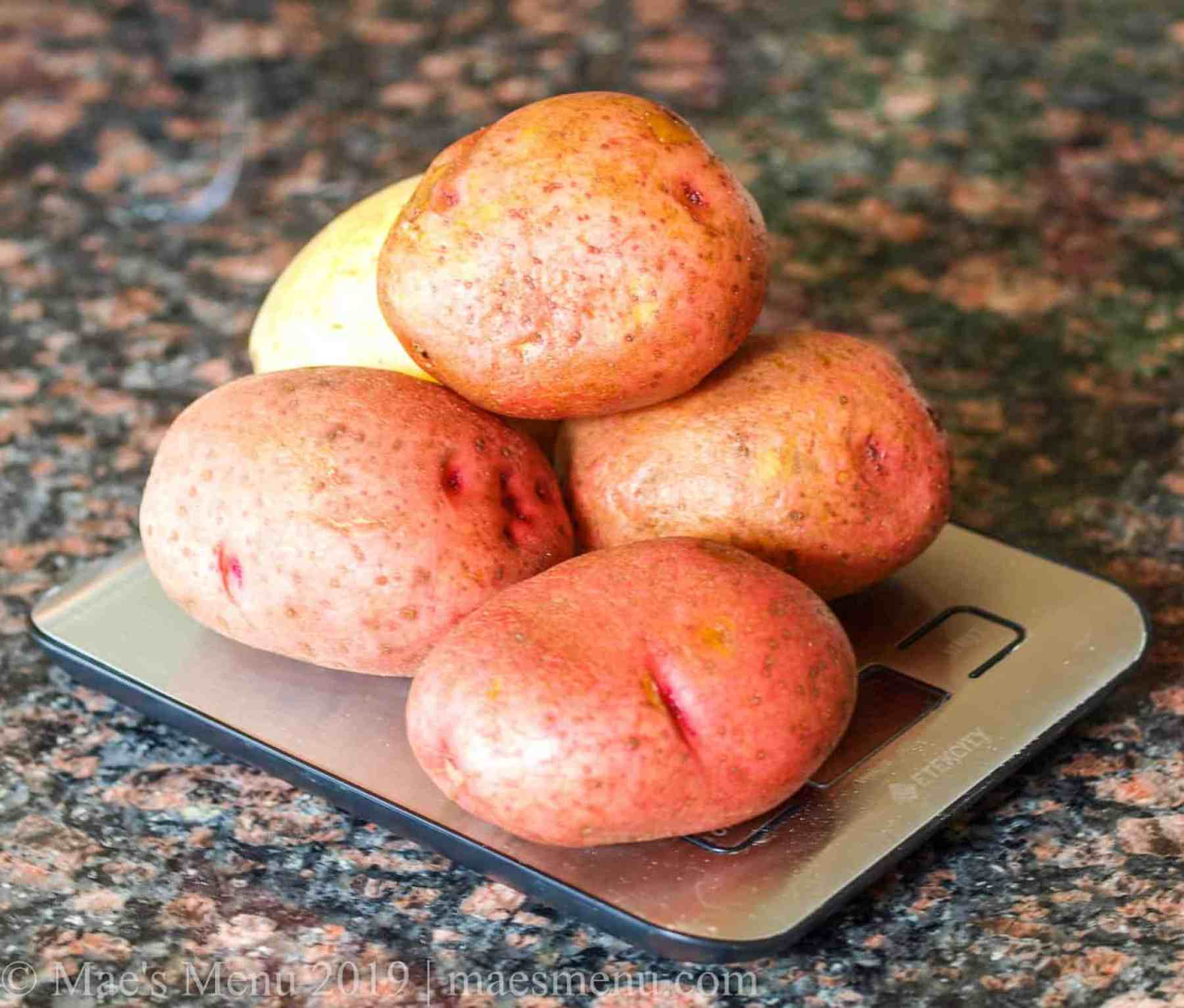 Yukon and red potatoes on a scale.