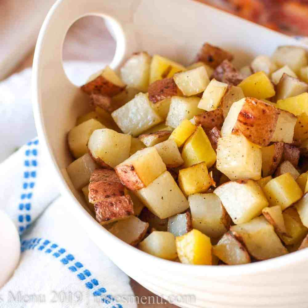 Large white bowl of diced hash browns.