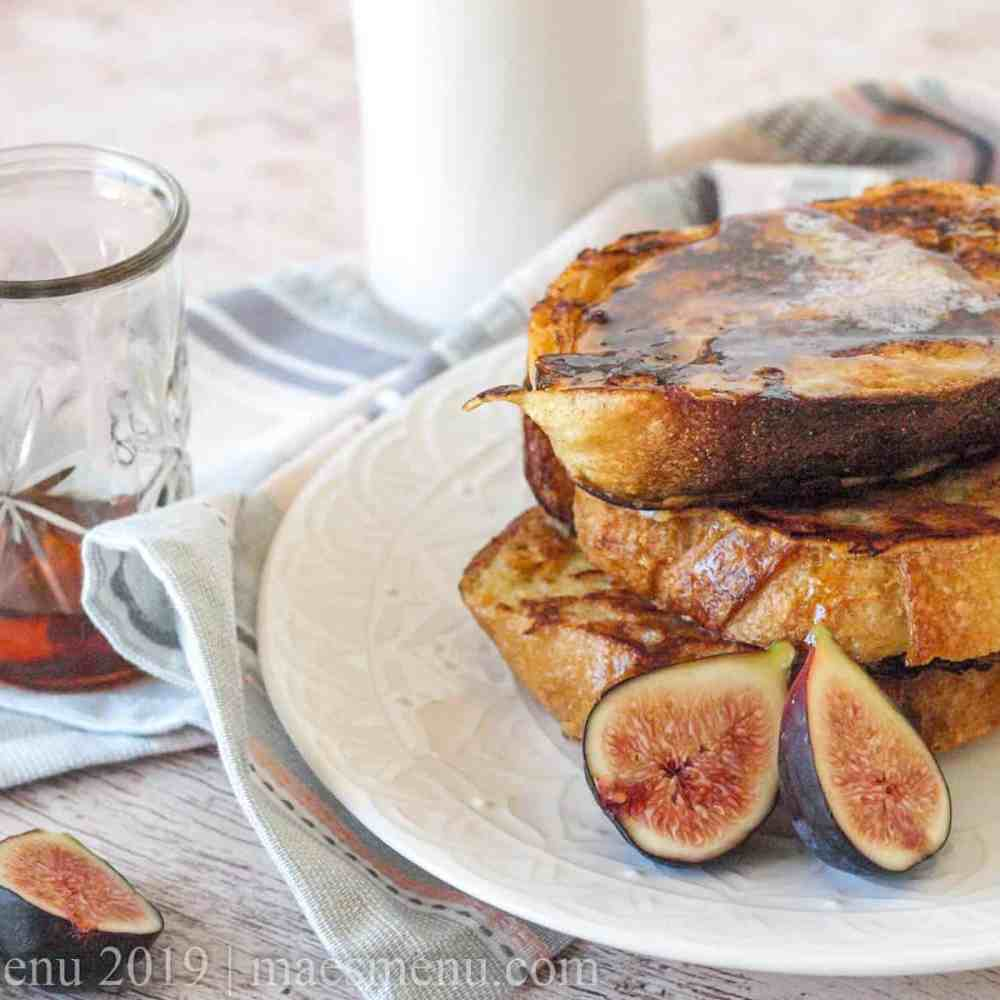 A stack of classic french toast next to figs, maple syrup, and a glass of milk.