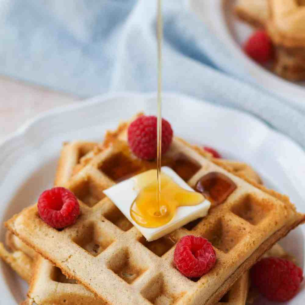 Syrup pouring over fluffy whole wheat belgian waffles.