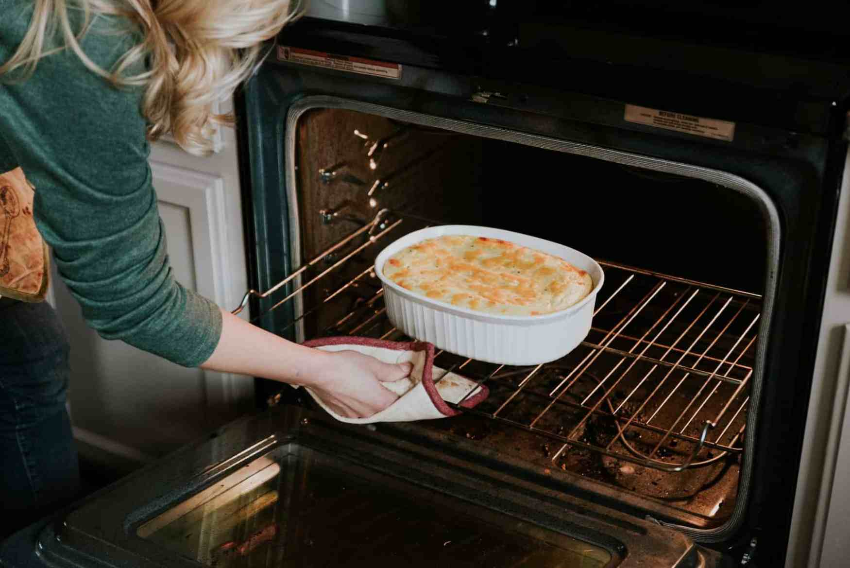 Pulling the mashed potato casserole out of the oven.