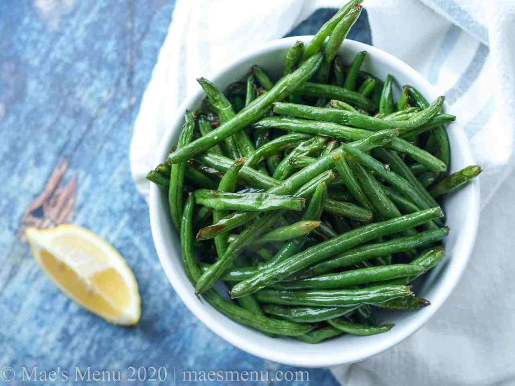 a large bowl of air fryer green beans with lemon.