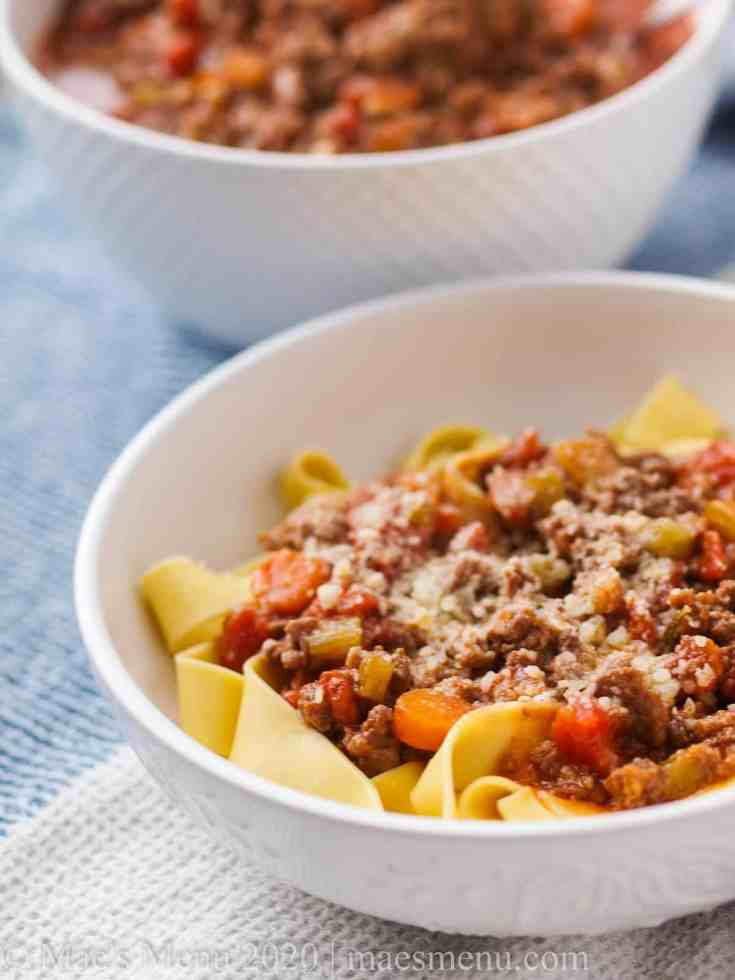a bowl of italian ragu over pasta next to the serving dish of the ragu.