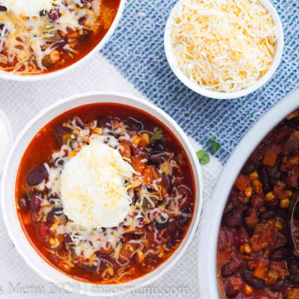 Two bowls of instant pot turkey chili next to a large pot of chili.