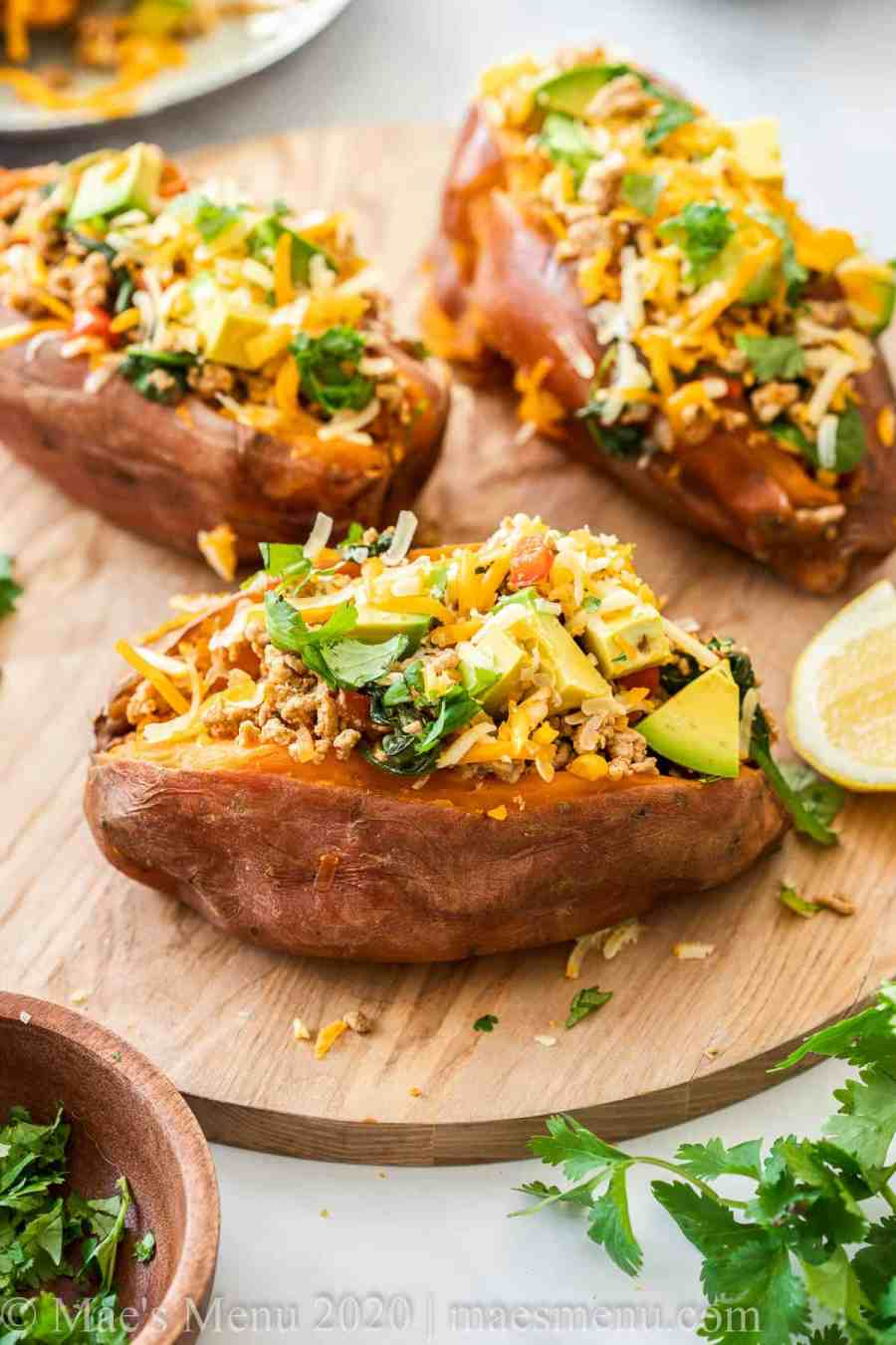 A wooden platter of taco stuffed sweet potatoes. Next to the platter sits cilantro, a lime wedge, and shredded cheese.