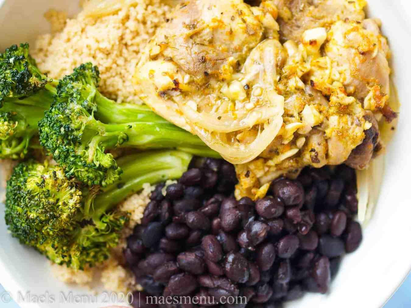An overhead shot of cuban sheet pan mojo chicken, black beans, and broccoli.