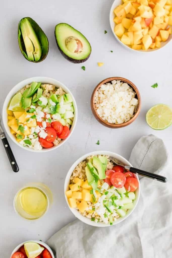 Bowls of Mango lime quinoa salad, a small container of feta cheese, a cup of chopped mango, a lime half, and avocado cut in half.