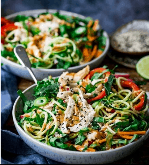 two large bowls of Thai chicken salad on a wooden table with a blue towel next to them.