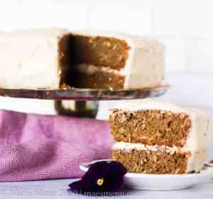 A cake stand with banana cake on it. One slice is cut out. A slice of cake sites on a small white plate in front of the cake.