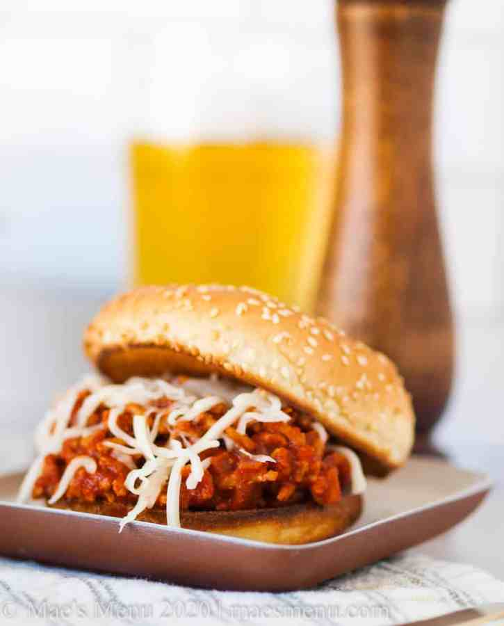 A small dish with a sloppy joe in front of a wooden pepper grinder and a glass of beer