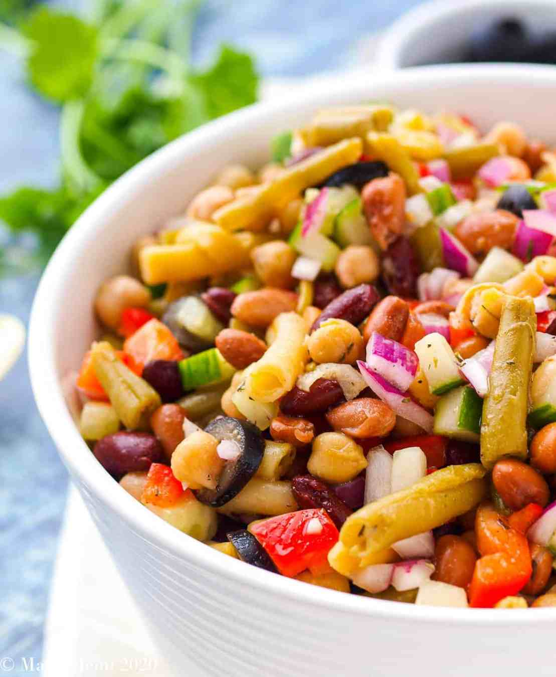 A side shot of a large white bowl of 5 bean salad.