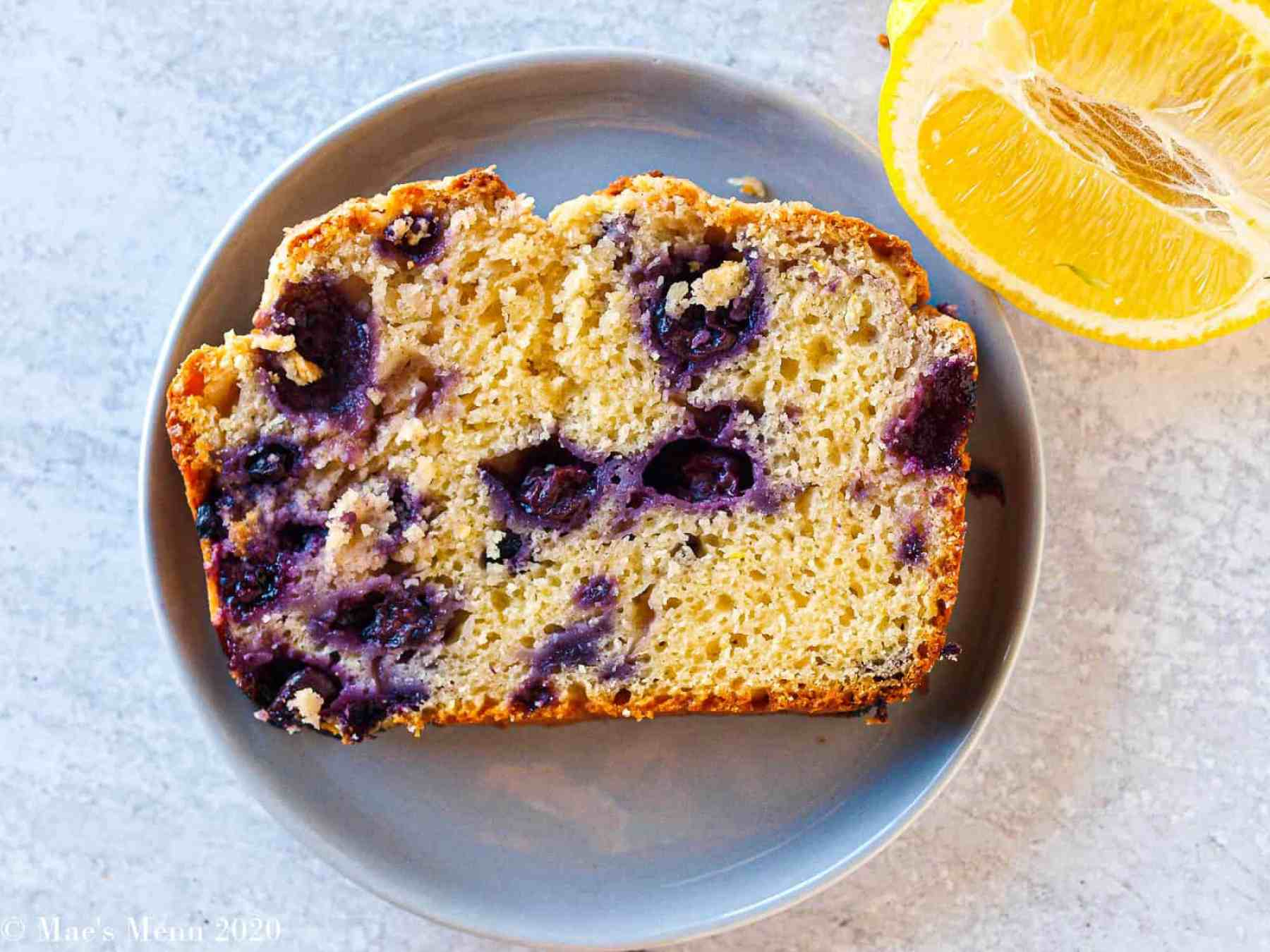 An overhead shot of a piece of blueberry lemon bread on a small grey plate.