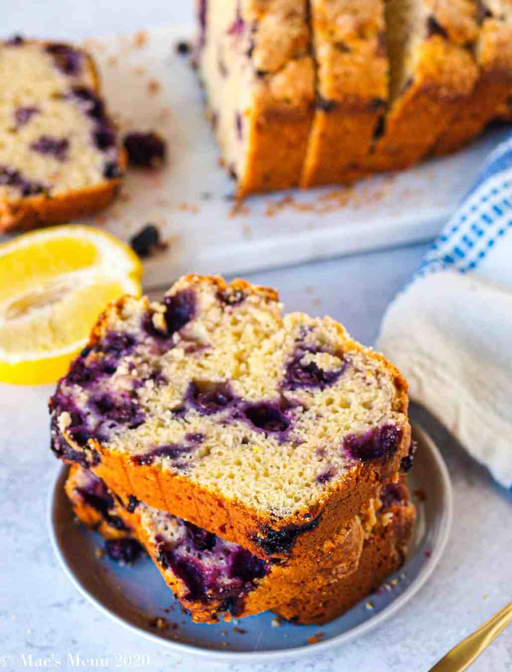 A small plate of lemon blueberry bread slices in front of a cutting board full of bread.