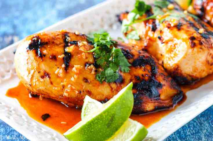 two large chicken breasts with the honey garlic spicy sauce on them sit on a white platter with lime slices next to them and cilantro on top of them.