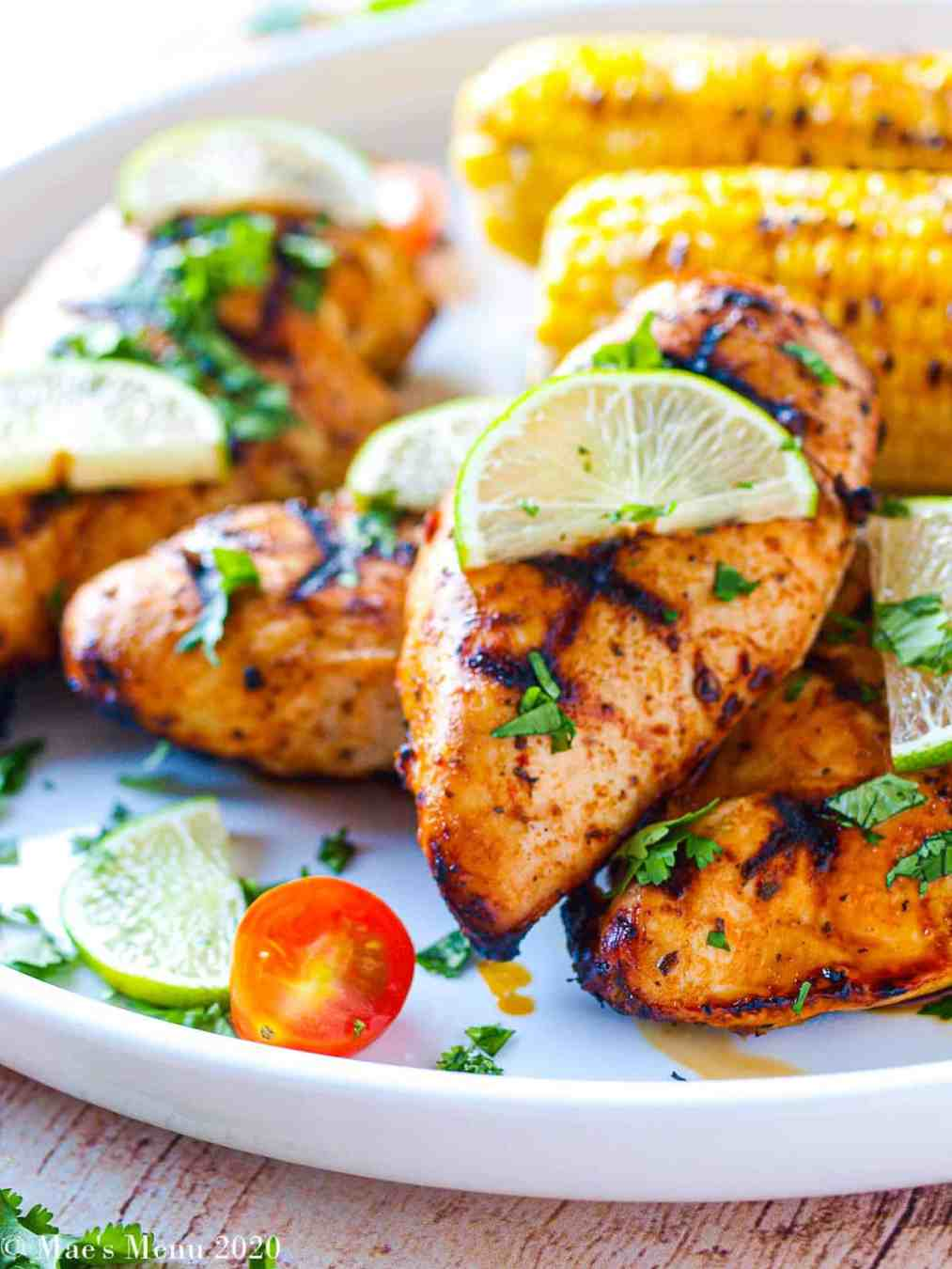 A large white platter with grilled chicken breasts with limes and cilantro on top and sliced tomatoes in front of the chicken. Behind the chicken sits grilled corn.