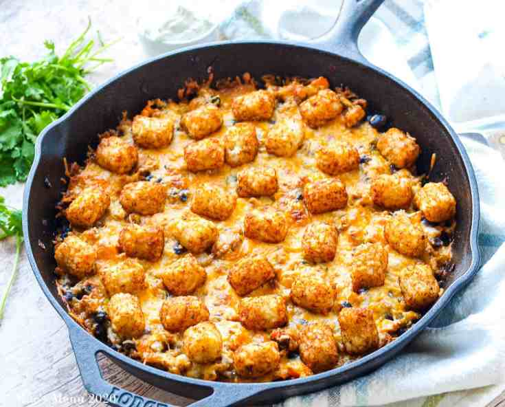 A large cast iron skillet full of taco tater tot casserole sitting on a white striped towel. Beyond the skillet on the left sits some herbs