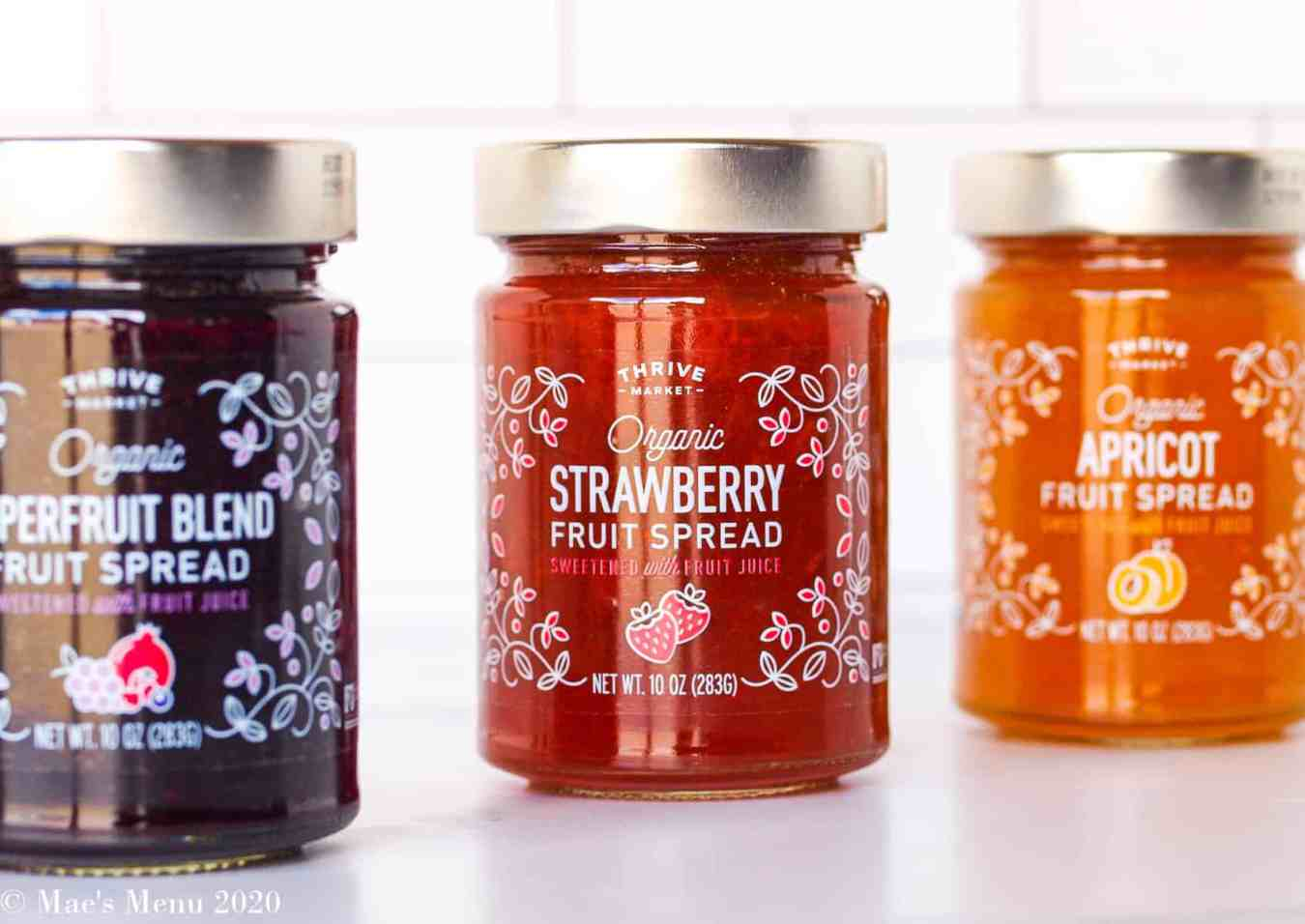 Three jars of thrive market fruit spread lined up on a counter with a white subway tile in the background.