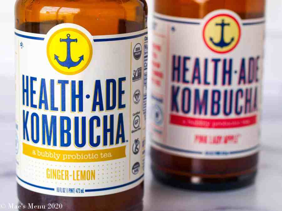 An up-close shot of two bottles of health-ade kombucha: one bottle of ginger lemon an the other of pink lady apple