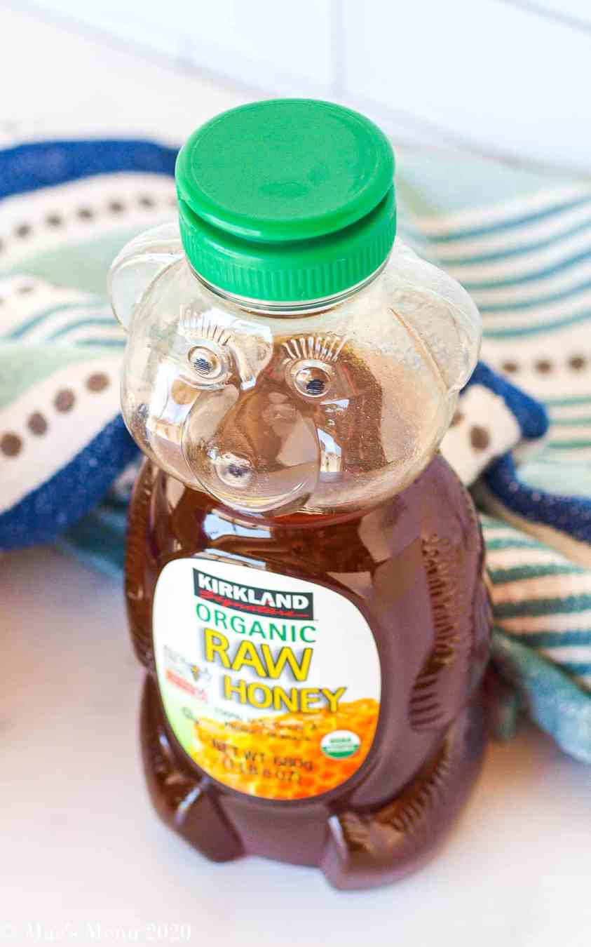 An overhead shot of a bottle of costco organic raw honey