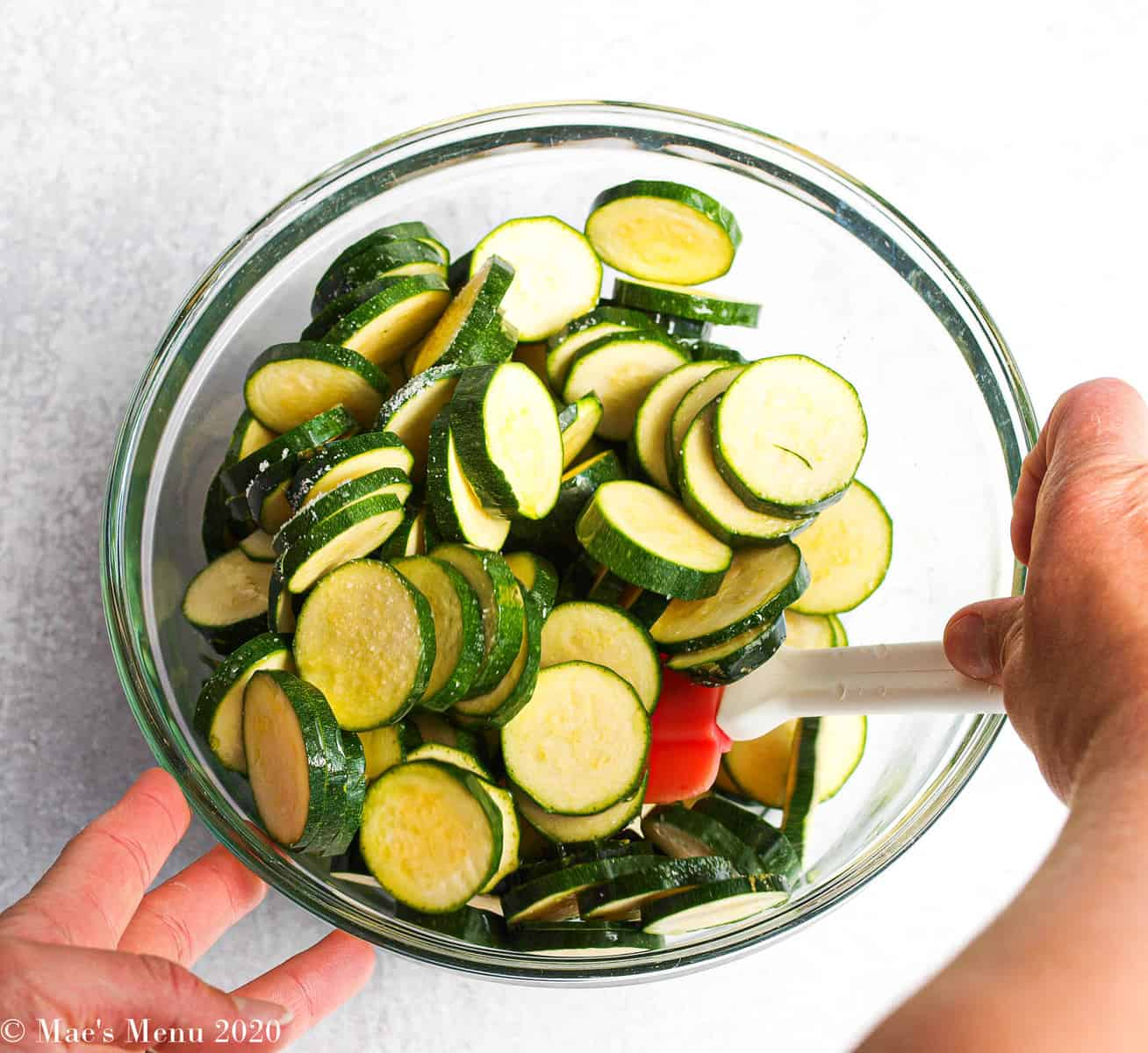 Stirring a bowl of zucchini coins in a mixing bowl