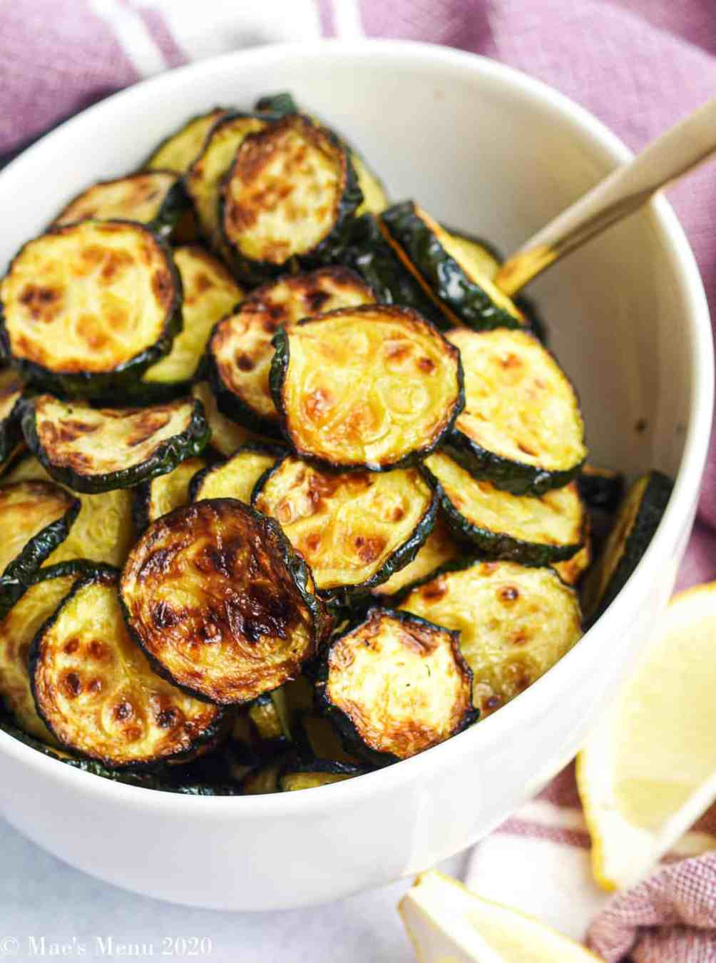A picture of a bowl of air fryer zucchini by lemon slices and a purple towel