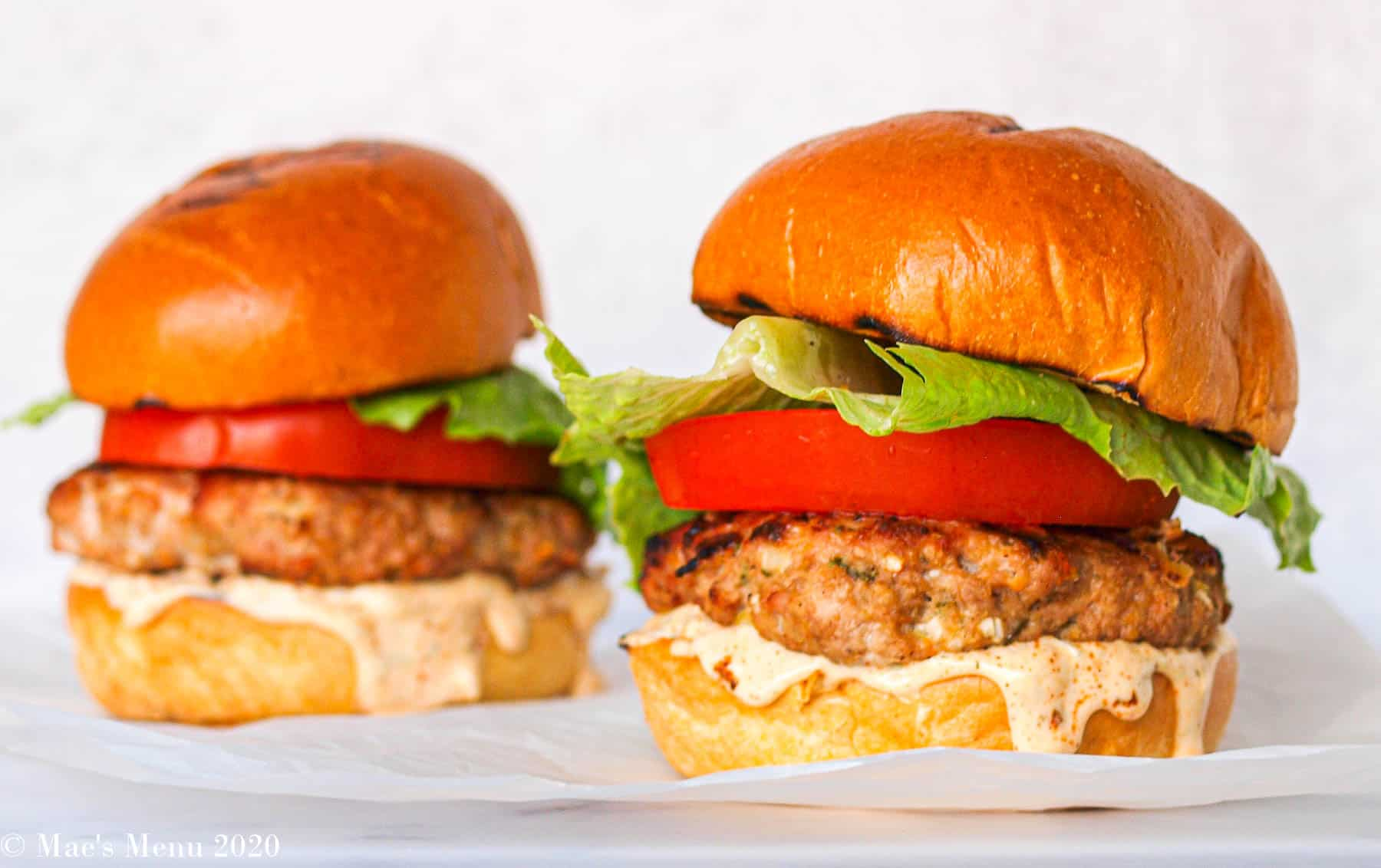 Two Jamaican Jerk Turkey Burgers on a white piece of parchment paper