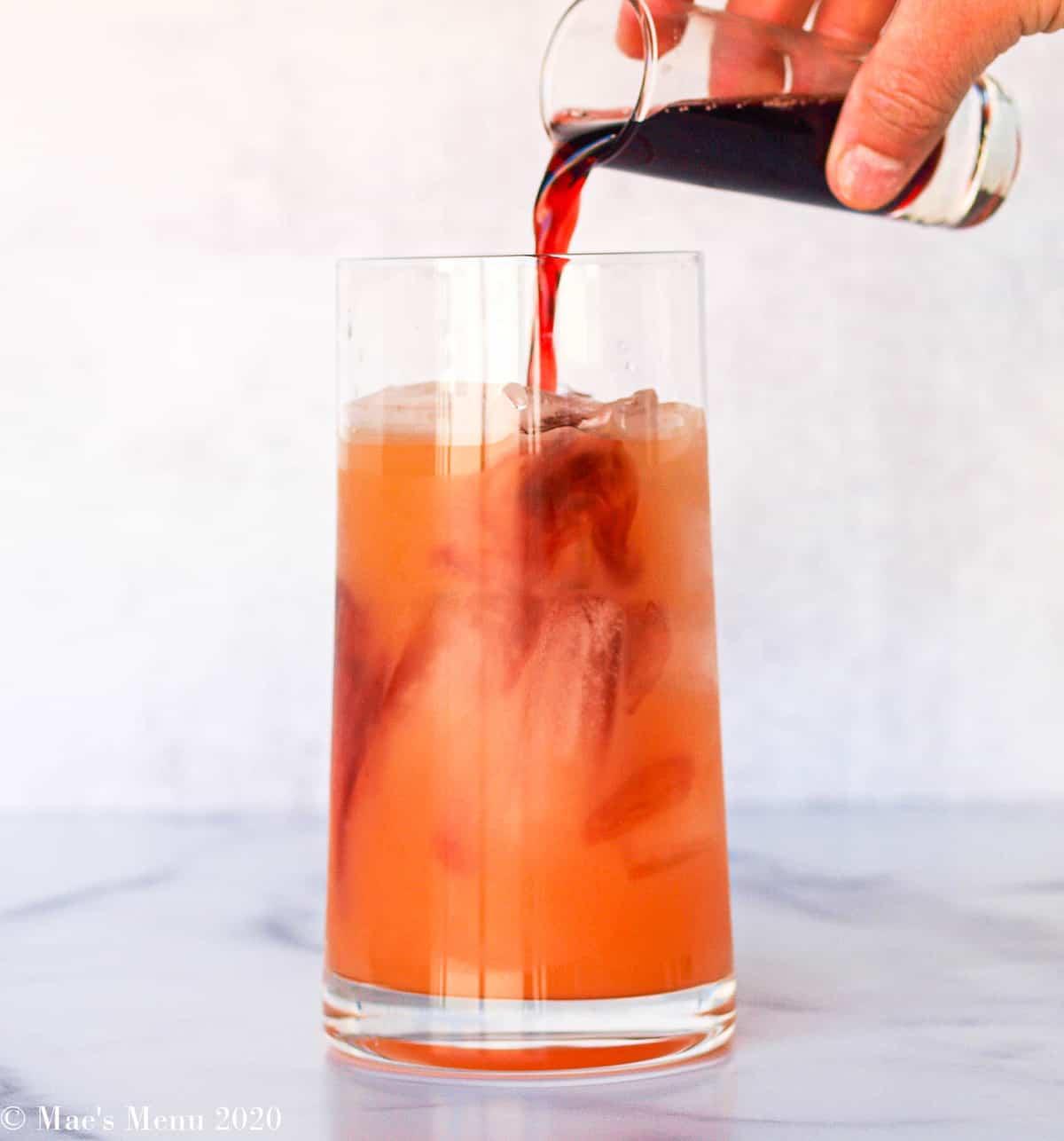 Pouring pomegranate juice into a glass of grapefruit juice